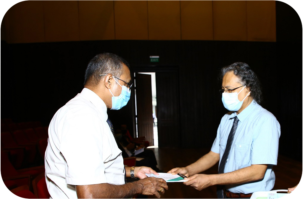 Dr. Chanakya Wijeratne presenting the book Sri Lankan Mathematics Competition 2019 - Detailed Solutions to the Secretary of the Ministry of Education Prof. Kapila Perera